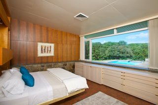 The master bedroom also overlooks the pool and the surrounding natural landscape.