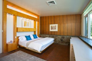 The master bedroom has wood paneling and built-in shelving.