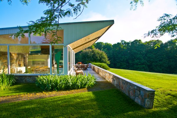 A dramatic triangular wooden truss extends the butterfly roof beyond the glass wall of the living room, also shading the stone-paved terrace. A low stone wall expands from the house into the surrounding landscape.