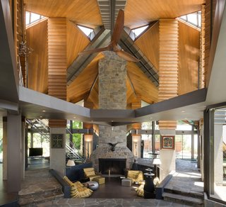 The ground level features a massive stone fireplace and a sunken conversation pit.