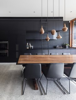 Perforated black panels became a recurring theme throughout the home. For instance, here they are employed on the walls of the kitchen.