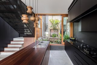 Large windows and floor-to-ceiling sliding doors have been integrated into the living space, providing an abundance of natural light, as well as easy access to the outdoor garden space. The perforated black walls are juxtaposed against warm wooden details like the countertop and pendant lights.