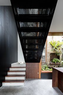 Perforated black metal has also been used in the design of the staircase.