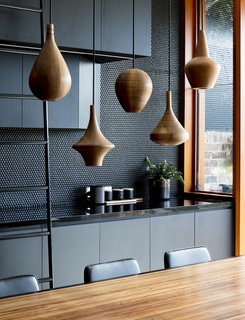 The perforated black walls are juxtaposed against warm wooden details.