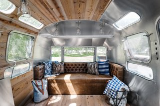 The updated interiors of the airstream are a mix of wood-paneling and the RV's iconic, shiny silver finish.