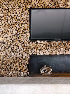 At the back of the pavilion is a double-stacked wood wall and fireplace with a TV.