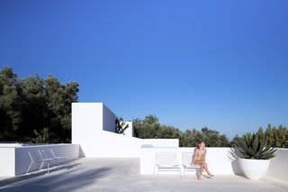 The rectangular edges of the whitewash rooftop terrace is perfectly integrated into the surrounding nature.