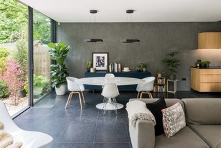 A wall of polished plaster extends to the rear, accentuating the ceiling height and adding a raw, textured finish to the otherwise polished interior space.