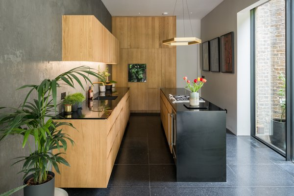 The kitchen pairs bespoke oak cabinetry with Gaggenau appliances and black Corian worktops that feature brass fittings by Vola for a polished, artistic look.