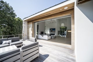 Collapsing walls were added to expand the open-plan living space on the main floor. This extended the space into an outdoor deck, which can now be enjoyed all summer long.