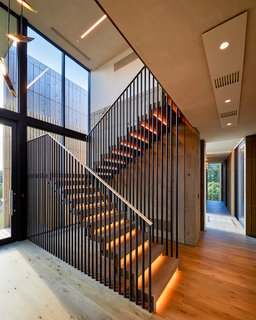 A double-height entryway features both stairs and an elevator which lead to the elevated main level. The stairway design echoes the exterior siding.