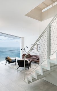 A central staircase with perforated metal treads and risers allows natural light to filter down from the roof-deck level through the center of the home.