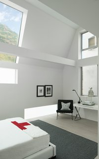 The guest-bedroom suite frames the hillside views above the street, increasing natural light and maintaining privacy.