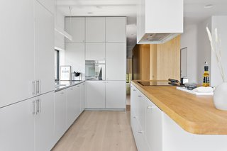 The kitchen features a sleek, modern mix of white millwork and natural wood countertops, and offers an impressive amount of storage.