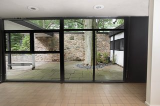 Floor-to-ceiling glass is used across the house, providing serene views of the home's forested surroundings.