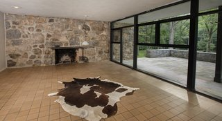 The living room features a natural flagstone inlay wall with a built-in fireplace juxtaposed against a row of windows.