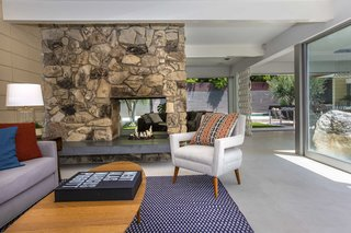 A two-sided stone fireplace divides the living room area.