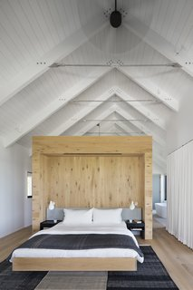 The master bedroom features vaulted ceilings and a light-wood wall to break up the space.
