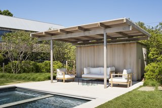 A covered sitting area at the edge of the pool.