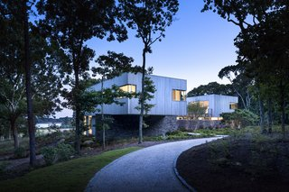 The home's siting marks a transition from the trees to the rolling fields that extend out to the distant waterfront.