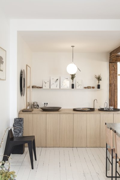 Benichou opened the space up by removing a wall and integrating the kitchen with the dining room. She then inserted a wooden counter that can now serve as a buffet when the gallery hosts dinners and events.