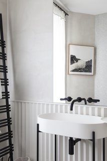 A sculptural pedestal sink accented by dark fixtures.