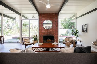 Abrick fireplace creates a strong centerpiece for the living space, which is bright an airy thanks to ample natural lighting.