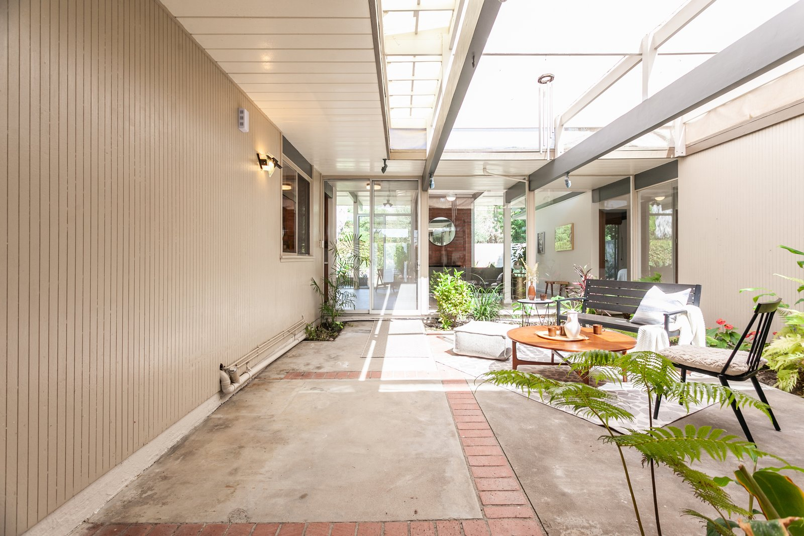 Outdoor, Small Patio, Porch, Deck, Gardens, and Concrete Patio, Porch, Deck The entrance leads to a spacious central atrium—a popular feature of many Eichler homes.     Photo 2 of 15 in An Updated Orange County Eichler Hits the Market at $1M