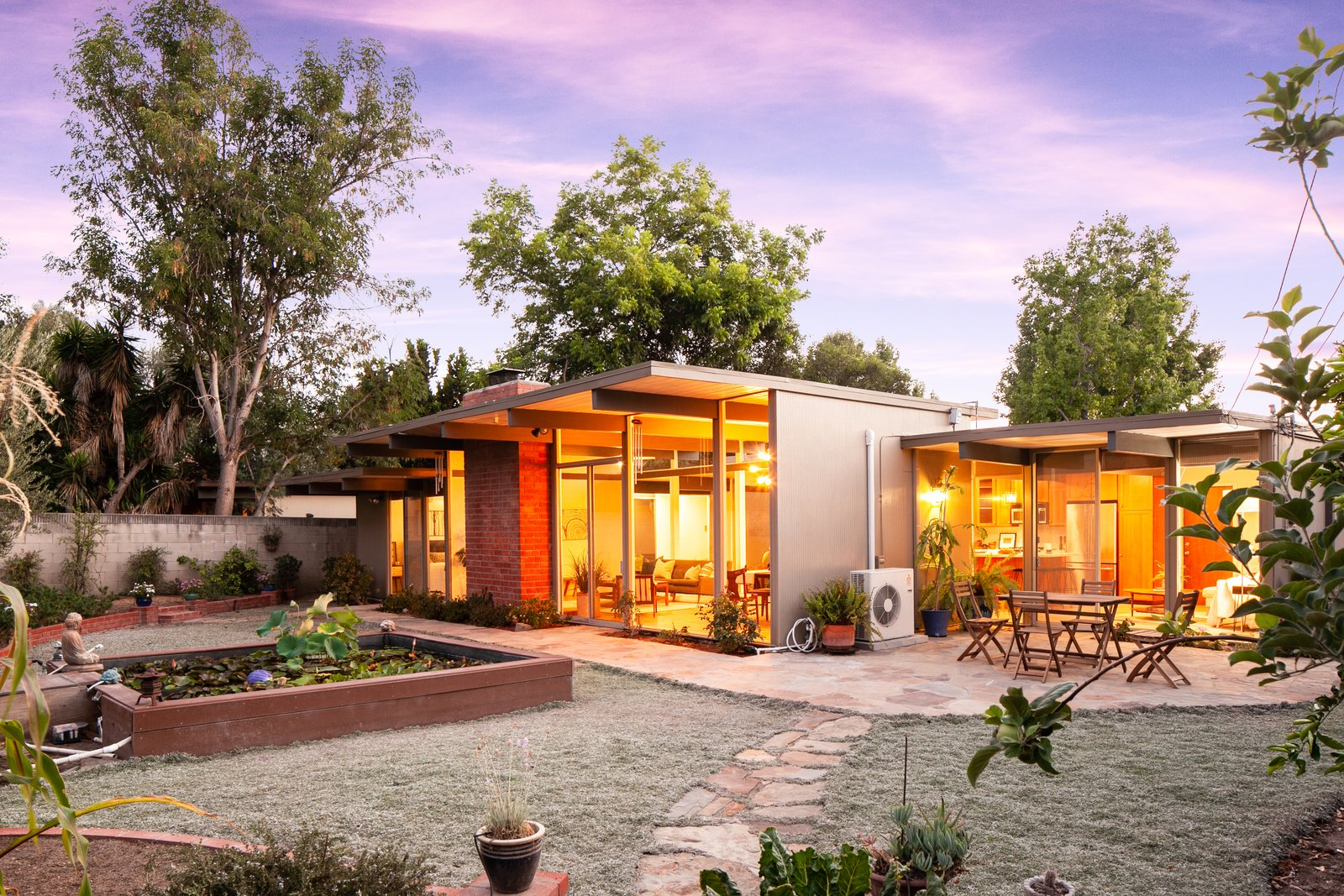 Outdoor, Concrete Fences, Wall, Hardscapes, Gardens, Small Patio, Porch, Deck, Trees, Horizontal Fences, Wall, and Back Yard The backyard at dusk.  Photo 14 of 15 in An Updated Orange County Eichler Hits the Market at $1M