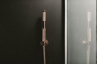 The interiors of the ensuite bathroom contrast dark colors with elegant copper Lusso fixtures.