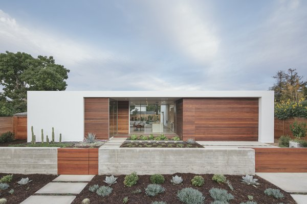 The astonishing transformation post renovation. The exterior palette consists of white stucco and Ipe wood, and the landscaping in the front yard is comprised of drought-tolerant plants, with a focus on succulents.