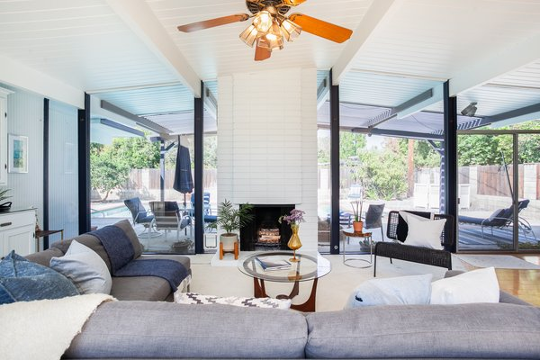 The home features an open-plan layout with a brick fireplace to anchor the space—a classic Eichler convention.