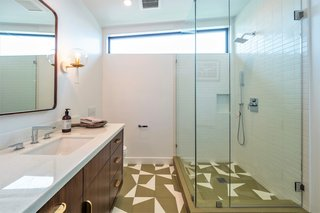 Graphic floor tiles, wood, and brass give the bathroom a polished, retro vibe.