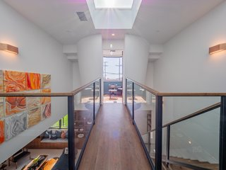 """Upstairs, the family level features four ensuite bedrooms plus a steel bridge which leads to a floating """"crow's nest,"""" which could be used as a private office or serene meditation space."""