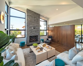 A step-up family room features a soaring, 16-foot, beamed ceiling with expansive glazing and a dramatic stone fireplace.