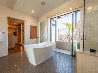 The large ensuite master bath opens to a balcony which has an outdoor shower and a green wall for privacy. High-end touches include wall-to-wall tiling, a steam shower, a freestanding soaking tub, and a Toto Neorest bidet toilet.