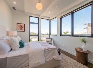 Globe pendant lighting and a beamed ceiling give this bedroom a midcentury feel.