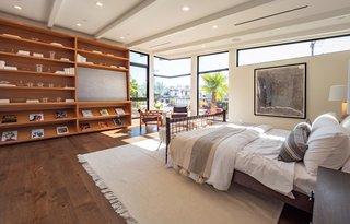The master suite is bright and airy with floor-to-ceiling windows, a beamed ceiling, built-in teak bookshelves, and an oversized walk-in closet with LED lighting.
