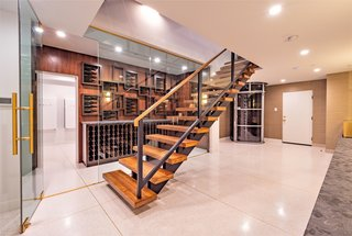 A temperature-controlled, glass-enclosed wine room with custom display shelving sits next to a large laundry facility with a pet shower.