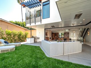 Outside, the lush landscaping includes palm trees and drought-tolerant succulents. The rear yard is prepped for a swimming pool and has a flat, grassy area with a hedge of trees for privacy.