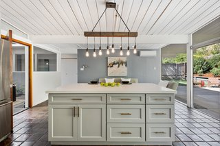 The expansive glazing in the kitchen brings both natural light and a sense of the outdoors into the space.