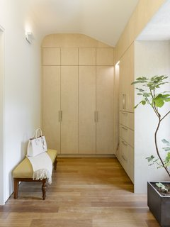 A large dressing room in the master suite shows off a uniquely customized built-in closet, which is perfectly inserted into the original curve of the ceiling.