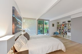 The large master bedroom features sliding doors to the outdoor space.