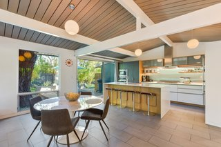 The kitchen opens to the living area, which has a recessed gas-flame fireplace and new full-height glass walls and sliding doors.