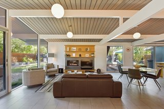 The post-and-beam construction is highlighted by the use of white paint against the ceiling's natural wood finish, creating a chic, modern look.