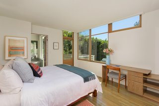 Downstairs, the sunlit master bedroom features an ensuite bath and a door leading to an outside terrace.