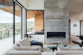 """The simple indoor/outdoor material palette consists of horizontal, natural cedar anchored by board-formed concrete. """"The cedar siding was an easy pick, adding some warmth to the gray concrete, but also making the house blend with nature. We chose a non-knotty cedar for a more modern appearance,"""" says Axboe."""