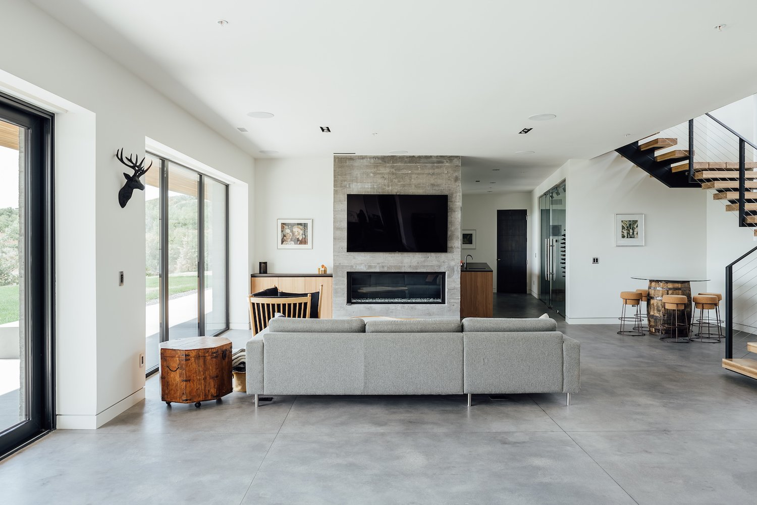 Living Room, Concrete Floor, Ceiling Lighting, Sofa, Recessed Lighting, Stools, Ribbon Fireplace, Chair, Table, Bar, Storage, and End Tables The lower level also features has a board-formed concrete fireplace.   Photo 13 of 14 in An Interior Designer's Utah Abode Blends Mountain Living With Scandinavian Style