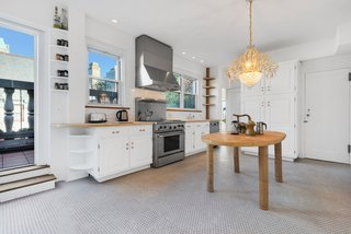 The bright and spacious kitchen features a penny-tiled floor and steps leading out to the wraparound terrace.