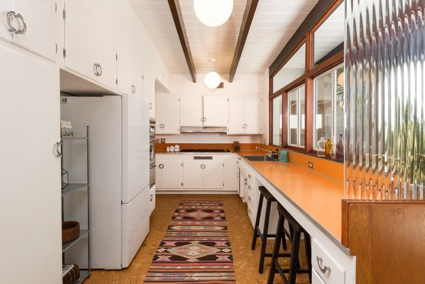 The original kitchen has vintage chrome hardware, a Western Holly oven, orange Formica counters, and cork flooring.